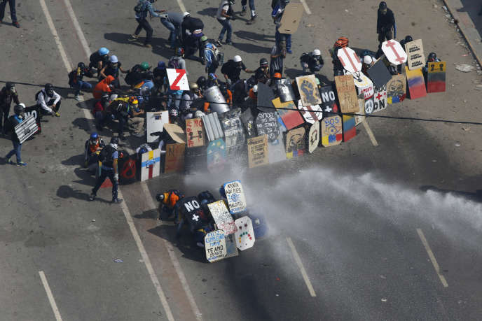 Des manifestants se protègent des canons à eau de la police anti-émeutes avec leurs pancartes, lundi 29 mai 2017 à Caracas, lors d'une manifestation contre le régime du président vénézuélien, Nicolas Maduro.