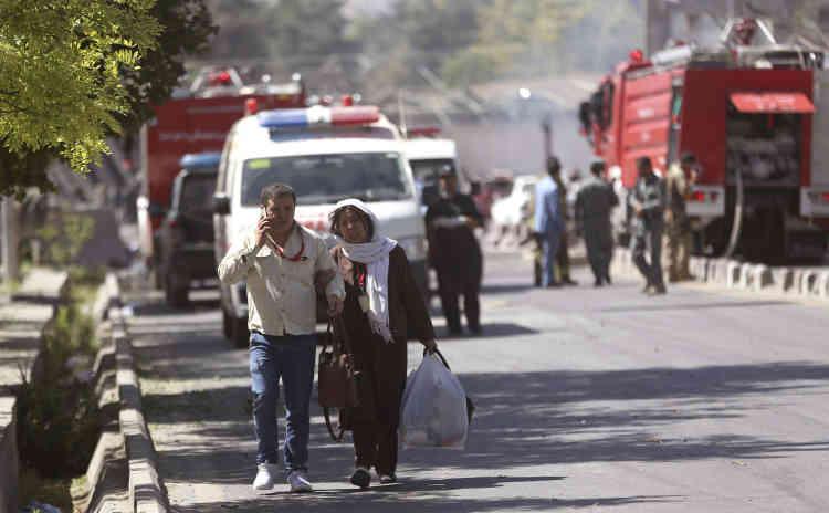 Des salariés de l'entreprise de télécommunication Roshan quittent le lieu où s'est produite l'explosion, à Kaboul, le 31 mai.
