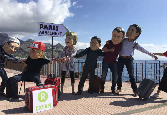 Des militants de l'ONG Oxfam mettent en scène Donald Trump se faisant prier par les autres dirigeants du G7 de respecter les accords de Paris.