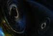 Vue d'artiste de deux trous noirs massifs spiralant l'un vers l'autre jusqu'à fusionner en un seul.