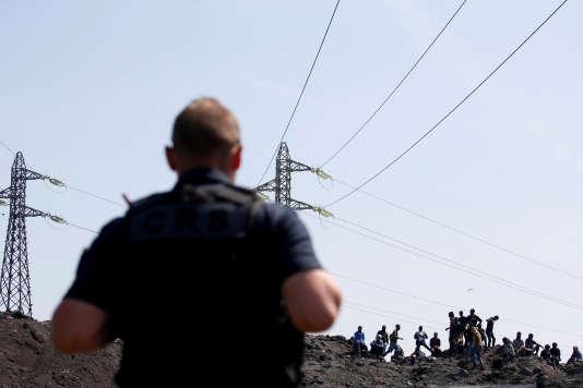 Un policier surveille des migrants à Calais, le 1er juin.