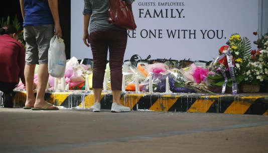 Des employés et des cliens du Resorts World Manila se recueillent dans l'entrée du bâtiment qui a été attaqué jeudi soir.