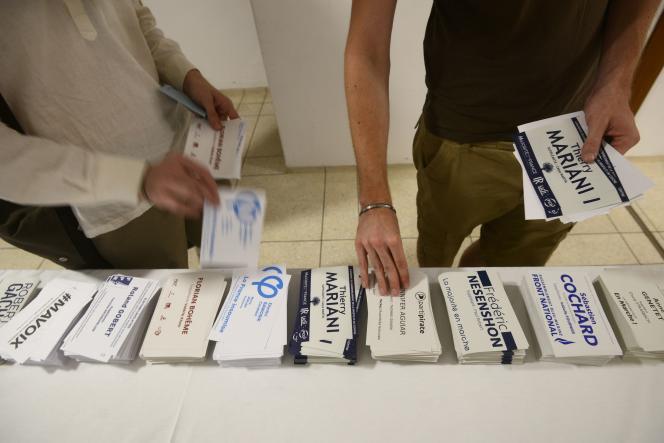 Des citoyens français se munissent de bulletins avant de voter au premier tour de l'élection législative, à New Delhi (Inde) le 4 juin.