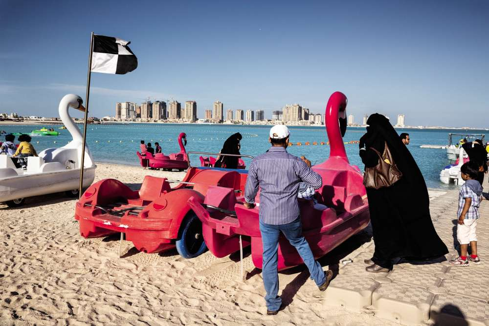 Une plage qatarie, en 2003, saisie par le regard de Martin Parr. Depuis son indépendance, en 1971, ses puissants voisins du golfe Arabo-Persique reprochent régulièrement au petit émirat de trop vouloir jouer sa partition en solo, en nouant dans un savant grand écart des liens privilégiés aussi bien avec les grandes puissances occidentales qu'avec lesgroupes islamistes. La crise, larvée depuis longtemps, a éclaté au grand jour, le 5juin, avec la décision de l'Arabie saoudite et des Emirats arabes unis d'instaurer un blocus économique afin de sommer le régime de Doha de rentrer dans le rang. Officiellement, ils lui reprochent de «soutenir le terrorisme». Mais en filigrane se pose aussi la question du rapport à l'Iran, l'autre grande puissance régionale, avec laquelle le Qatar partage un champ de gaz. Riyad juge Doha trop complaisant avec son grand rival.