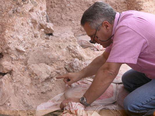 Jean-Jacques Hublin pointe vers le crâne écrasé dit « Irhoud 10» en phase d'extraction: les orbites sont visibles juste sous l'extrémité de son doigt.