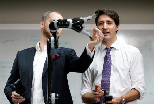 Le premier ministre canadien Justin Trudeau (d) participe à la démonstration d'une main robotique avec Charles Deguire co-fondateur de Kinova Robotics à Boisbriand, Québec, le 24 mars 2017.
