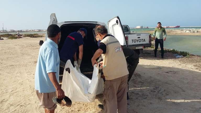 Chemseddine Marzoug (dr.) aide des agents de la protection civile à charger le corps d'un migrant noyé au large des côtes libyennes et échoué à Zarzis, le 2 juin 2017.