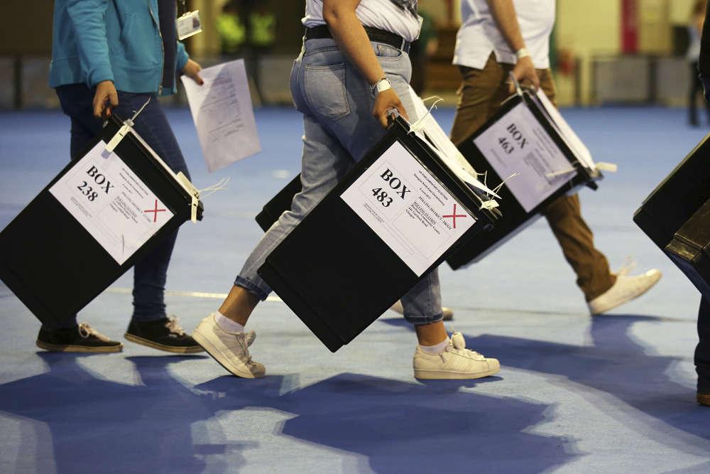 Trois femmes portent des urnes avant le dépouillement, à l'Emirates Arena deGlasgow, en Ecosse.