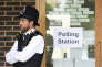A police officer is stationed outside a polling station at Cubitt Town Infant and Junior School on the Isle of Dogs in London, as people cast their votes in the general election, Thursday June 8, 2017. (Victoria Jones/PA via AP)