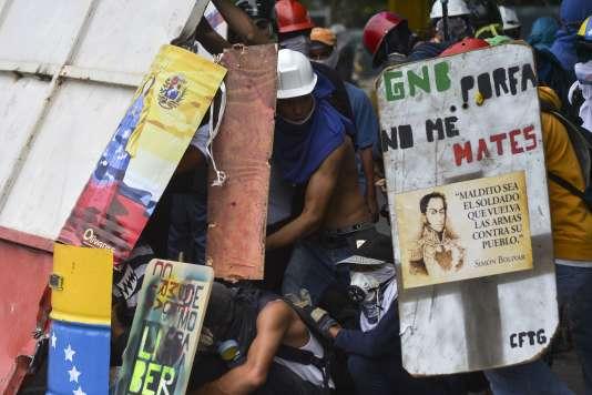 Des manifestants se protègent avec des boucliers, dont l'un proclame « Police, s'il vous plaît ne me tuez pas», à Caracas, le 7 juin.