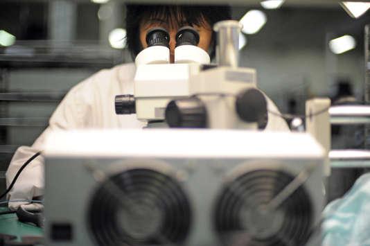 Un technicien de laboratoire travaille sur microscope.