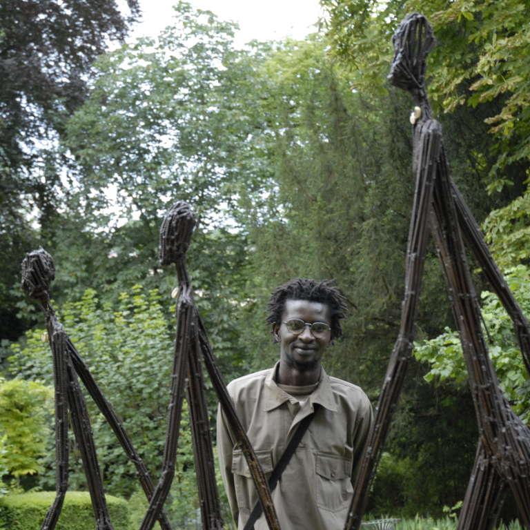 """Portrait de Ndary Lo posant derrière sa sculpture """"Les trois hommes qui marchent"""", en juin 2007."""