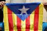 Un militant brandit le drapeau catalan sur lequel il a écrit la date du référendum exigé par le gouvernement régional, à Barcelone le 9 juin.