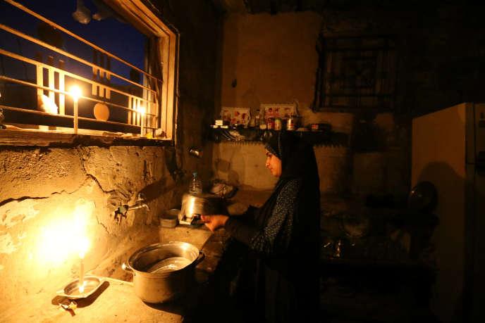 Une jeune fille palestinienne fait la vaisselle durant une coupure d'électricité dans la bande de Gaza.