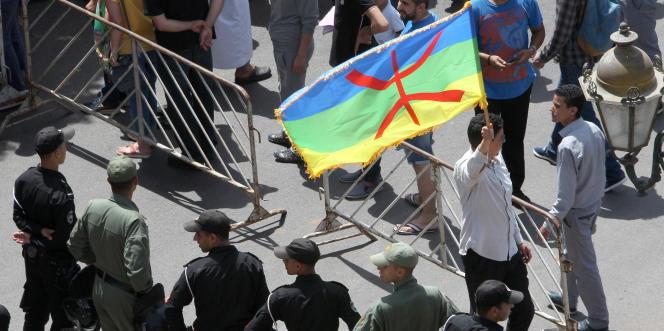Un manifestant brandit un drapeau berbère.