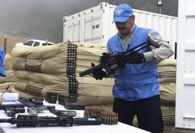 Un membre des Nations Unies en Colombie tient une arme remise par des rebelles des FARC au camp provisoire d'Elvira, à Buenos Aires, le 13 juin 2017.
