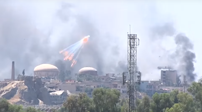 Capture d'écran de la vidéo tournée à Mossoul, le 3 juin, par Kurdistan 24, montrant des explosions d'obus et la retombée de flammèches incendiant les immeubles.