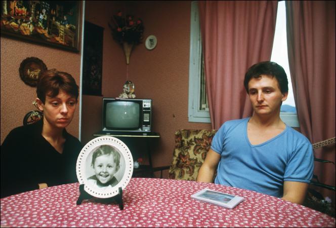 Christine et Jean-Marie Villemin, les parents du petit Grégory, 4 ans, retrouvé noyé le 16 octobre 1984, pieds et poings liés dans la Vologne, sont assis, le 23 novembre 1984, à la table de leur salle à manger sur laquelle est posée une assiette à l'effigie de leur enfant.