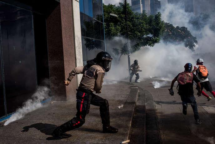 Un garde national poursuit des manifestants cagoulés lors d'une manifestaion contre le président Maduro à Caracas, le 20 mai.