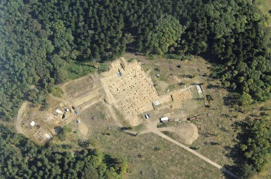 Vue aérienne de l'esplanade, dite du Parc aux chevaux, où l'on distingue l'empreinte d'un grand édifice quadrangulaire en cours de fouille et les trous de poteaux de bois de son péristyle.