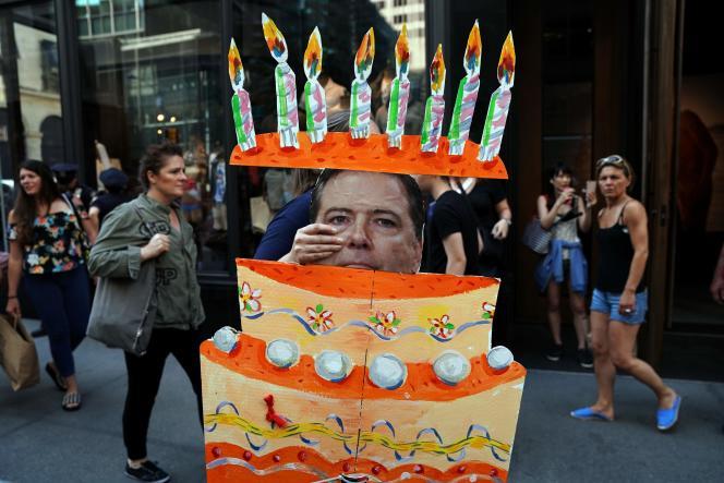 Un manifestant anti-Trump brandit une pancarte montrant l'ex-directeur du FBI, James Comey, sortir d'un gâteau, à New York, le 14 juin, jour de l'anniversaire du président américain.