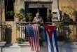 Un habitant de la vieille Havane se tient sur son balcon, orné des drapeaux américain et cubain, le 19 décembre 2014, deux jours après que les deux pays eurent, contre toute attente, annoncé la volonté de normaliser leurs relations diplomatiques.
