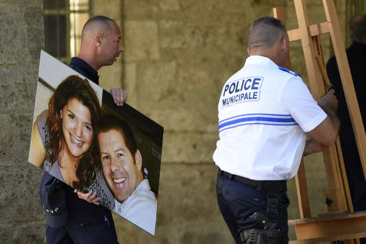 Policemen take off the picture of French policeman Jean-Baptiste Salvaing and his partner Jessica Schneider who were killed outside their home in Magnanville, after the tribute at the Place de la Mairie (city hall square) in Pezenas, southern France, on June 20, 2016. On June 13 assault, 25-year-old Larossi Abballa, previously convicted for jihadism, killed a police officer and his partner before streaming his claim for the murders live on Facebook. / AFP PHOTO / SYLVAIN THOMAS