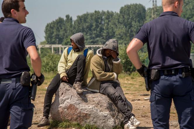 Des policiers surveillent des migrants à Calais, le 1er juin.