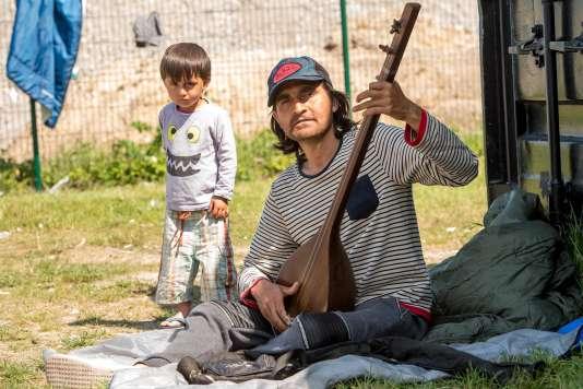 Ismaïel, un Afghan de 35 ans, joue du dotâr (un luth à deux cordes) aux côtés de son fils, à Calais le 1er juin.