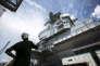Jeremy, appareilleur de bord, attend que la grue lui descende les pièces qui ont été démontées. Chantier de modernisation du porte-avions Charles de Gaulle, Toulon, juin 2017.