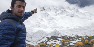 In this image released by Lymbus, Kilian Jornet from Spain points towards Mount Everest in 2017. Even the hardiest few who scale the treacherous slopes of Mount Everest cut short celebrations for some well-deserved rest. Not Kilian Jornet. He somehow still had enough legs left to scale the mountain again a few days later. (Lymbus via AP)