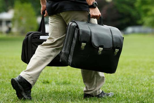 Un aide de camp tranporte la valise contenant les codes nucléaires, à la Maison Blanche, le 17 juin.