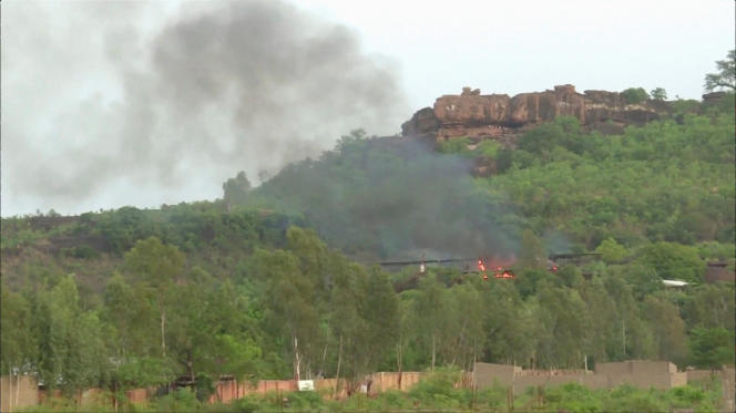 Des flammes sont visibles près de la piscine après l'attaque de l'hôtel Le Campement par des hommes armés, à Dougourakoro, le 18 juin 2017.