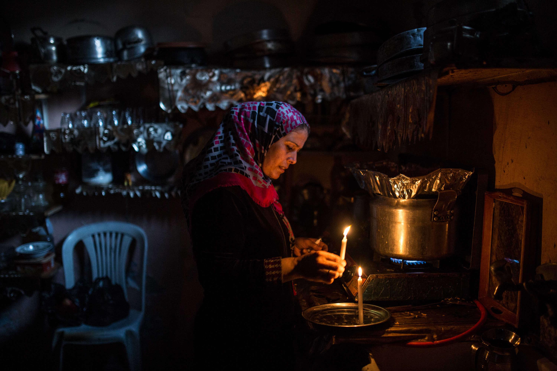 Aman Abu Mohaisen prépare l'iftar (rupture du jeûne de ramadan) pour ses sept enfants. Elle ne peut pas s'offrir un générateur, ni s'inscrire auprès d'un particulier en possédant un. Sa seule source de lumière, lorsqu'il n'ya pas d'électricité, est la bougie ou des LED quand elles sont rechargées.