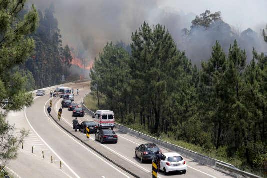 Des véhicules officiels sur l'autoroute IC8, à proximité des flammes, près de Pedrogao Grande (Portugal), le 18juin 2017.