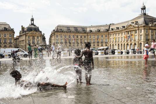 Des enfants se rafraîchissent sur un miroir d'eau, dans le centre-ville de Bordeaux, le 27mai 2017. Le département de la Gironde sera lundi en vigilance orange à la canicule.