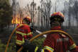 """Portuguese firefighters work to stop a forest fire from reaching the village of Figueiro dos Vinhos central Portugal, Sunday, June 18, 2017. Portugal's president says the country's pain """"knows no end"""" as it mourns at least 61 people killed in the deadliest wildfire in memory. (AP Photo/Paulo Duarte)"""