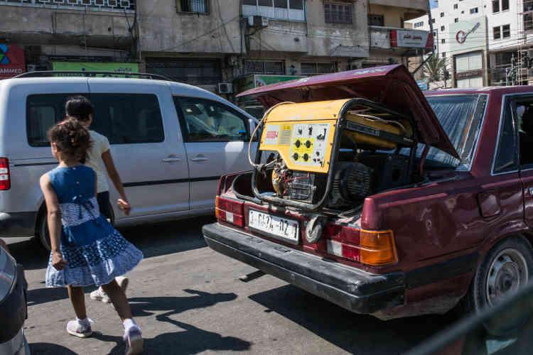 Un Gazaoui transporte un générateur dans le coffre de sa voiture.