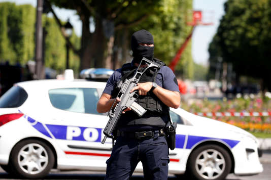 Un policier masqué sur les Champs-Elysées, lundi 19 juin.