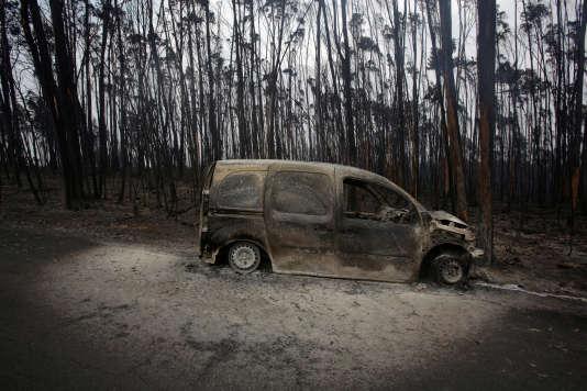 Une camionnette brûlée au milieu d'une forêt incendiée sur une route menant à Pedrogao Grande, au Portugal, le 19 juin.