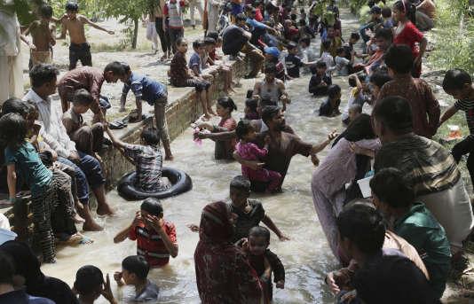 Des familles se rafraîchissent dans l'eau d'un ruisseau lors d'une canicule à Lahore, au Pakistan, le 4 juin.