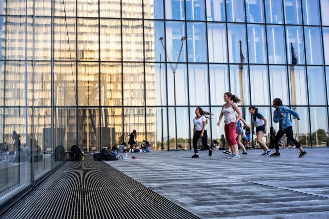Un groupe de jeunes filles utilise les reflets des vitres de la Bibliothèque nationale de France, à Partis, pour répéter des pas de danse.