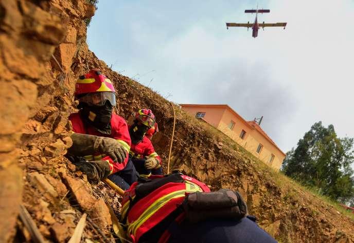 Des pompiers s'abritent avant un largage d'eau par un Canadair dans la région de Pedrogao Grande, le 20juin 2017.