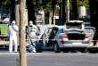 Des membres de la police scientifique examinent le véhicule qui a percuté, le 19 juin, un fourgon de gendarmerie sur les Champs-Elysées.