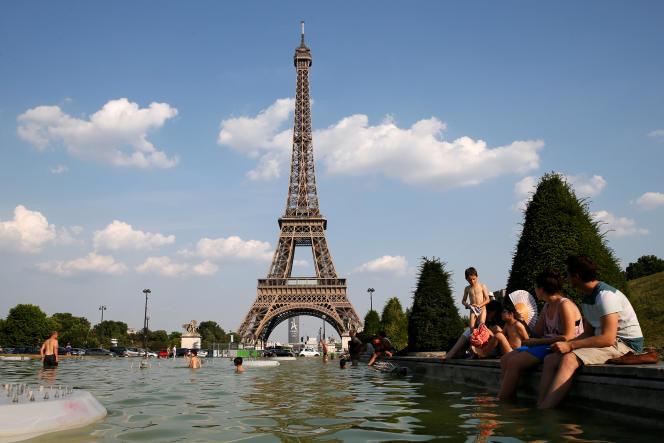 «En suivant le périphérique, on peut mesurer l'ampleur de l'édification réalisée, ou en cours, aux environs des portes de la capitale, une zone qui, à l'origine, devait être une ceinture verte.» (Des Parisiens tentent de se rafraîchir dans les fontaines près de la tour Eiffel, le 21 juin.)