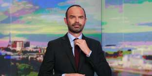 French Prime Minister Edouard Philippe arranges his tie prior to taking part in the evening news broadcast of French TV channel TF1, in June 21, 2017, in the TF1 studios in Boulogne-Billancourt, near Paris, following the announcement of the new French government. / AFP / BENJAMIN CREMEL