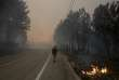 A man walks through a local road during a forest fire near Louriceira, Portugal, June 20, 2017. REUTERS/Miguel Vidal