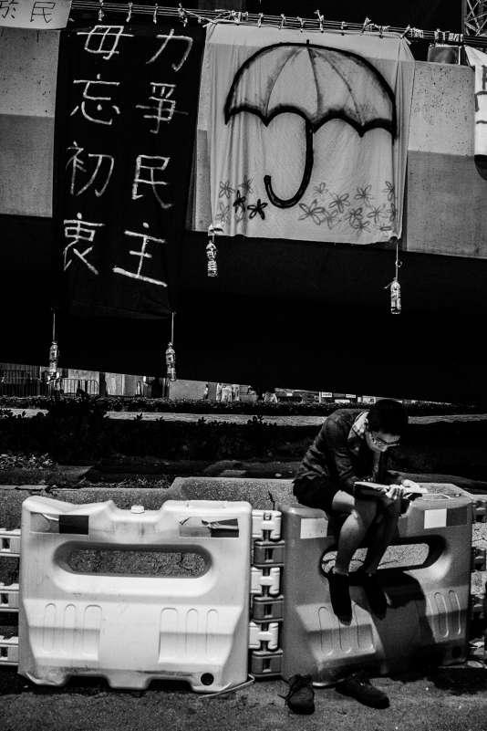 Un étudiant hongkongais étudie sous des banderoles vantant le « mouvement des parapluies » qui, en septembre et en octobre 2014,s'est opposé auprojet de Pékin de limiter la portée du suffrage universel pour l'élection du chef de l'exécutif de Hongkongen 2017.