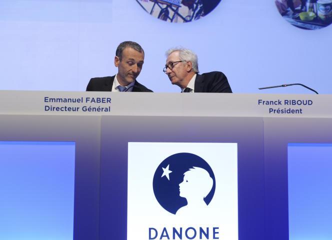 Le directeur général de Danone Emmanuel Faber et le président du conseil d'administration Franck Riboud, et l'ancien logo du groupe, le 27 avril à Paris.