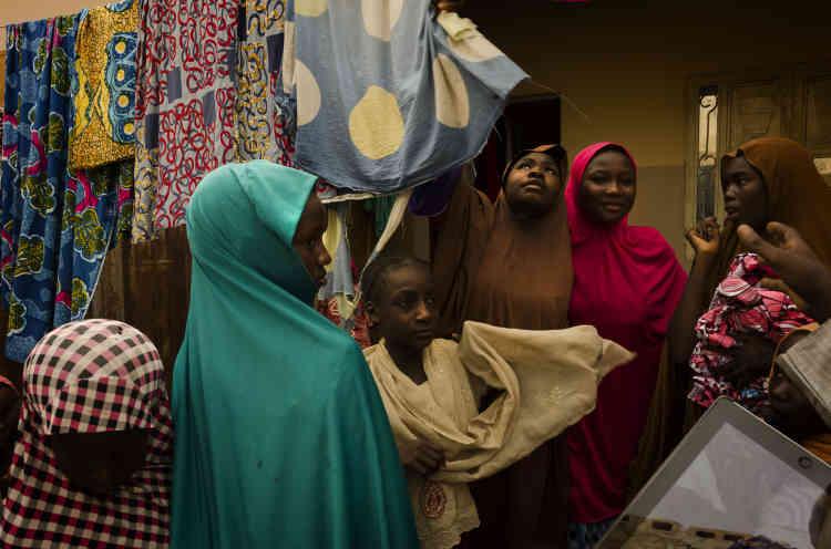 Au marché de Maiduguri, les invitées de Khadija choisissent le tissu de leur tenue.